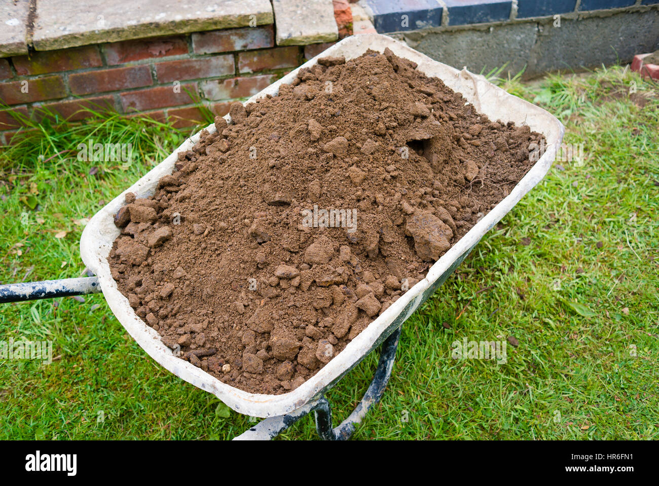 Wheelbarrow filled with spoil dug out of a new outdoor pond - Stock Image