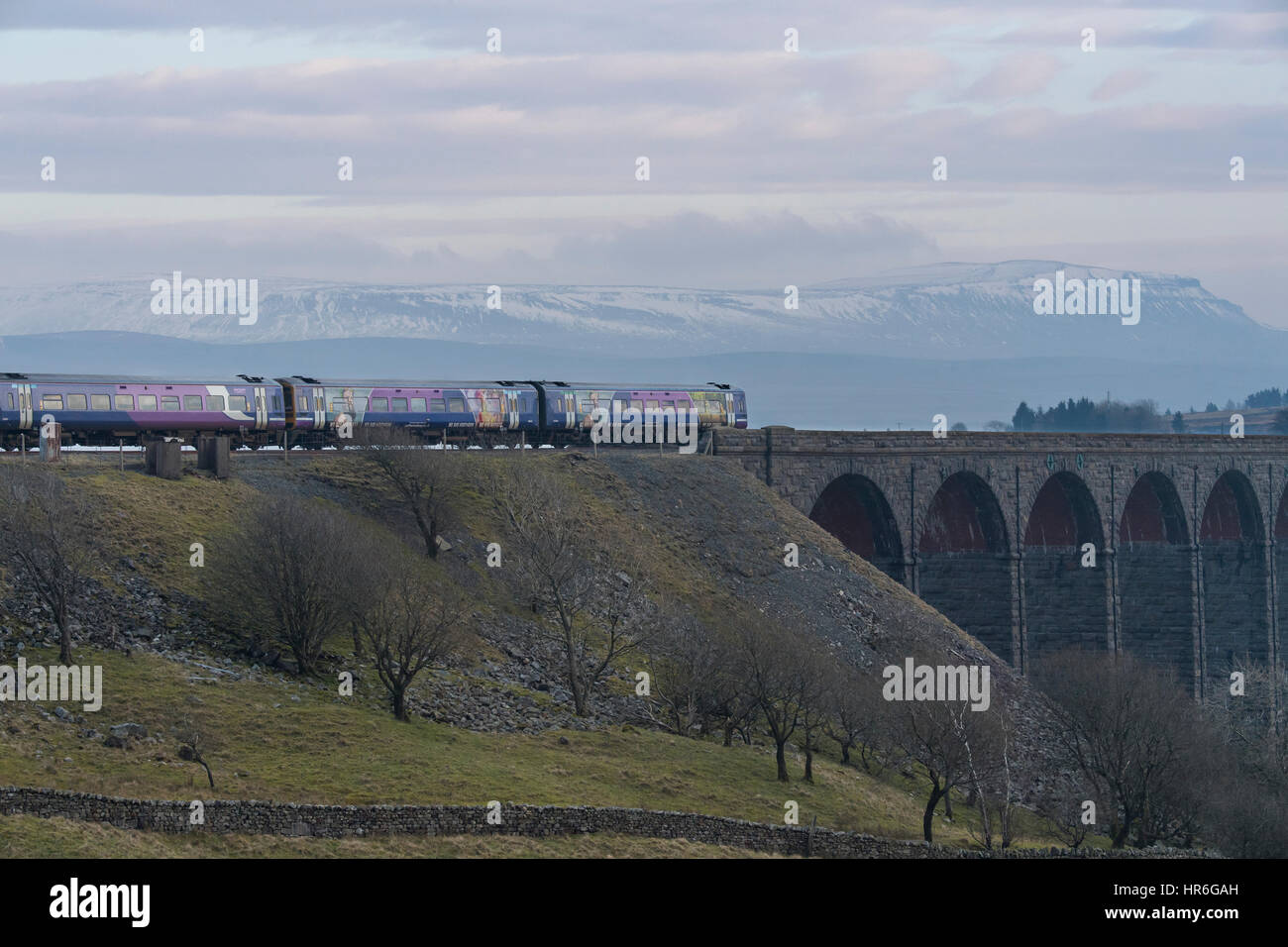 An Arriva Rail Northern passenger diesel train going across the Ribblehead Viaduct on a grey winter day with snow - Stock Image