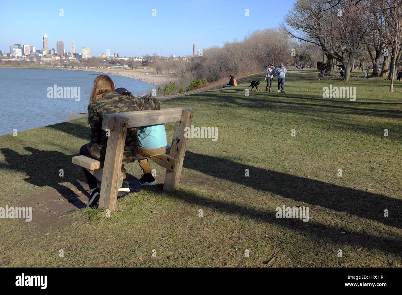 Cleveland, Ohio skyline view enjoyed by a couple at Edgewater Park on a rare warm February afternoon - Stock Image