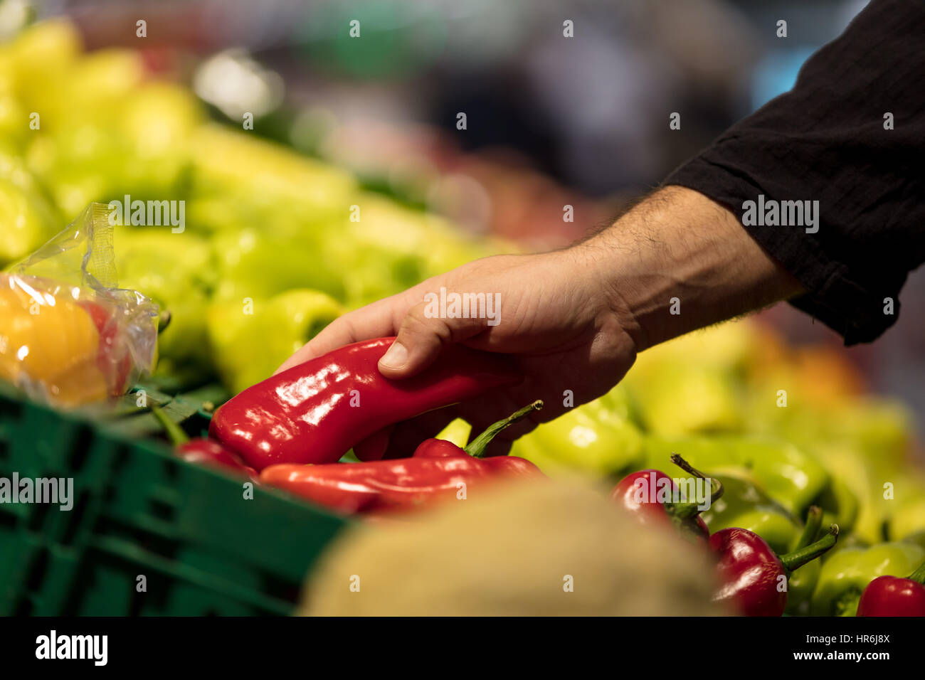 sale, shopping, food, consumerism and people concept - woman with basket buying bell peppers or paprika at grocery - Stock Image