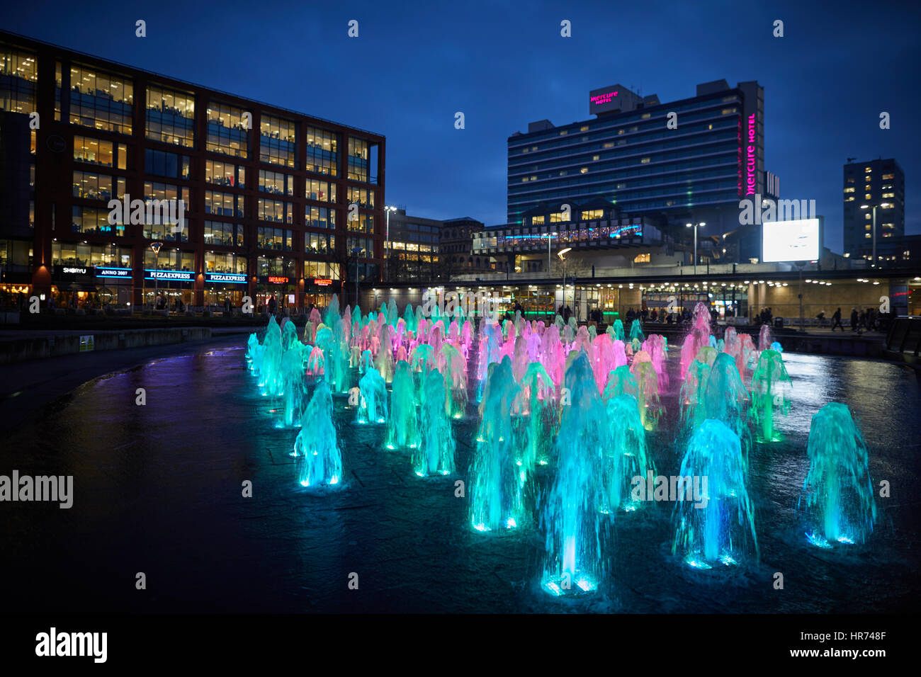 MANCHESTER City Centre, Piccadilly Gardens landmark water fountain display lights at night. - Stock Image