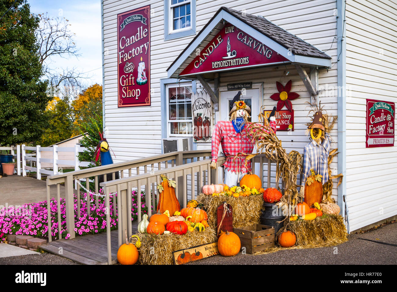 A candle shop with a fall arrangement of pumkins and scare crows in Walnut Creek, Ohio, USA. - Stock Image