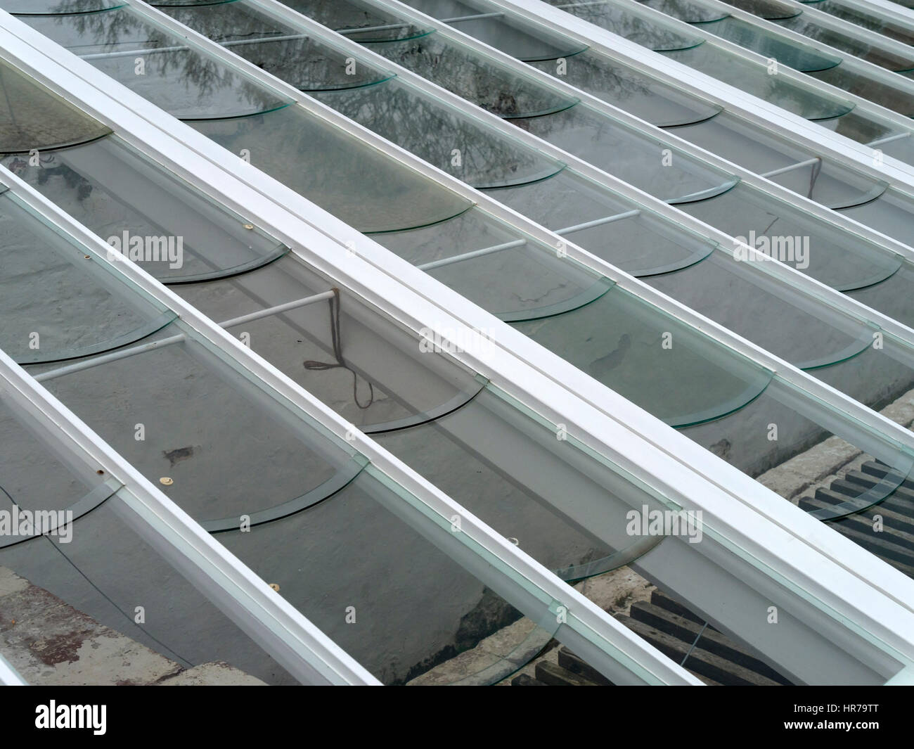 Cold frame or greenhouse roof with specially cut glass window panes which have curved edges which direct rainwater - Stock Image