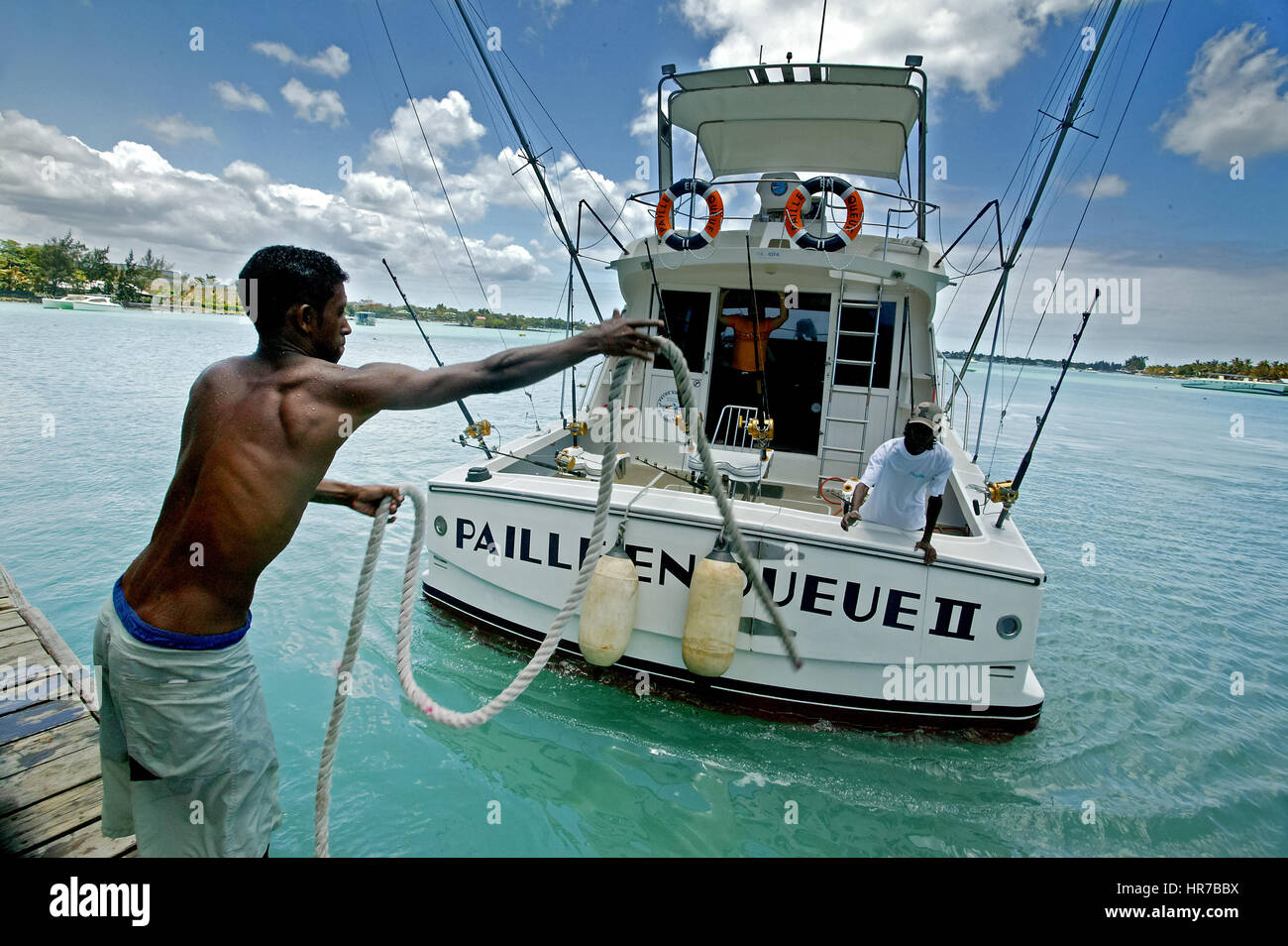 Mauritius, Grand Baie, deep sea fishing, bathing, blue water, boat, local boy helping at the pier for the deep sea - Stock Image