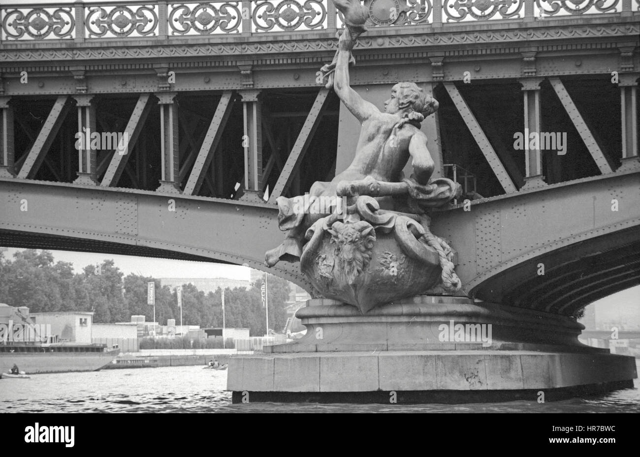 The Mirabeau Bridge over the Seine River feature bronze sculptures on the piles. This figure on the right bank is - Stock Image