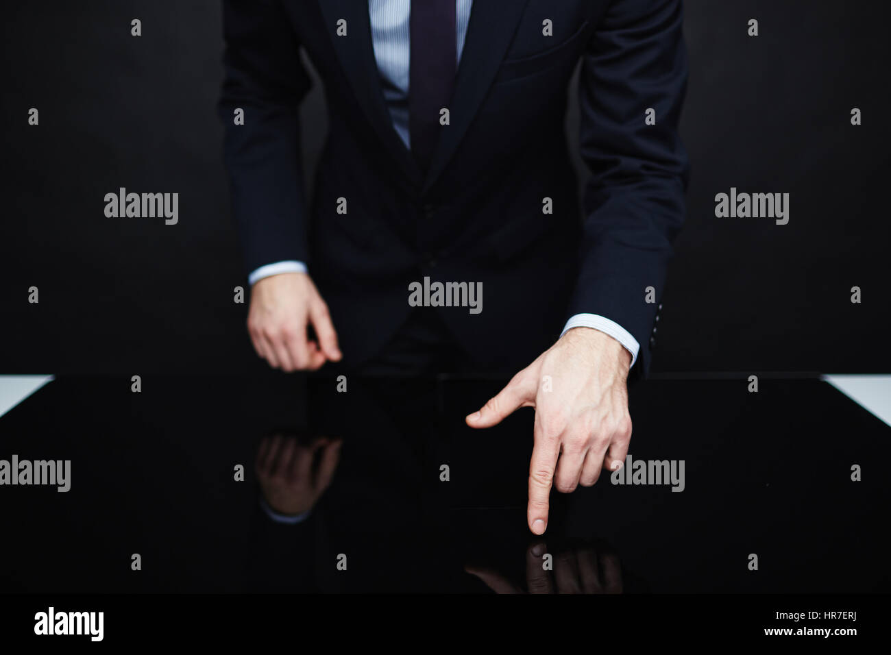 Closeup portrait of unrecognizable authority figure wearing business suit standing leaning on table  making persuasive - Stock Image