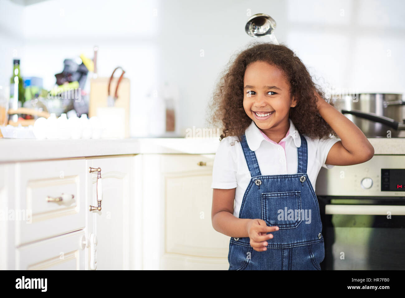 f5ffce5b321b Cute little girl in denim jumpsuit standing next to kitchen oven and  looking at camera with