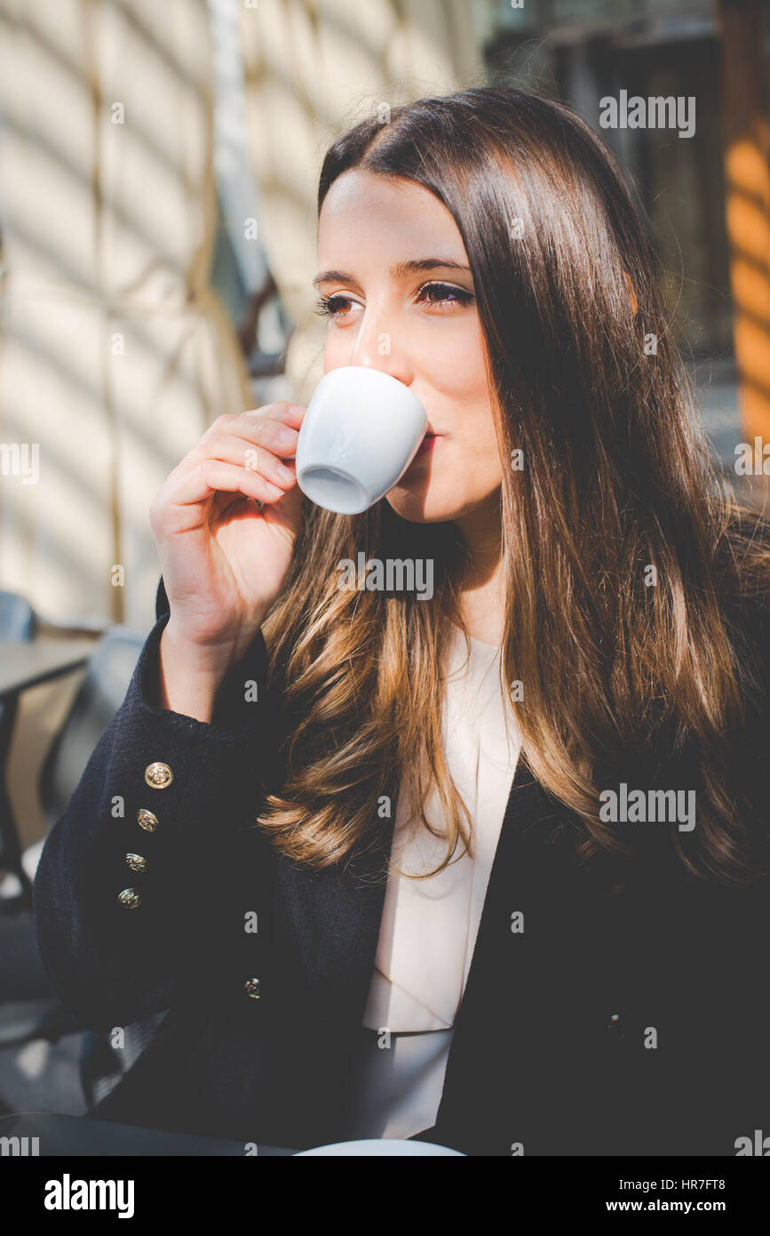 young authentic business woman in the city for a buisness travel - coffee break - Stock Image