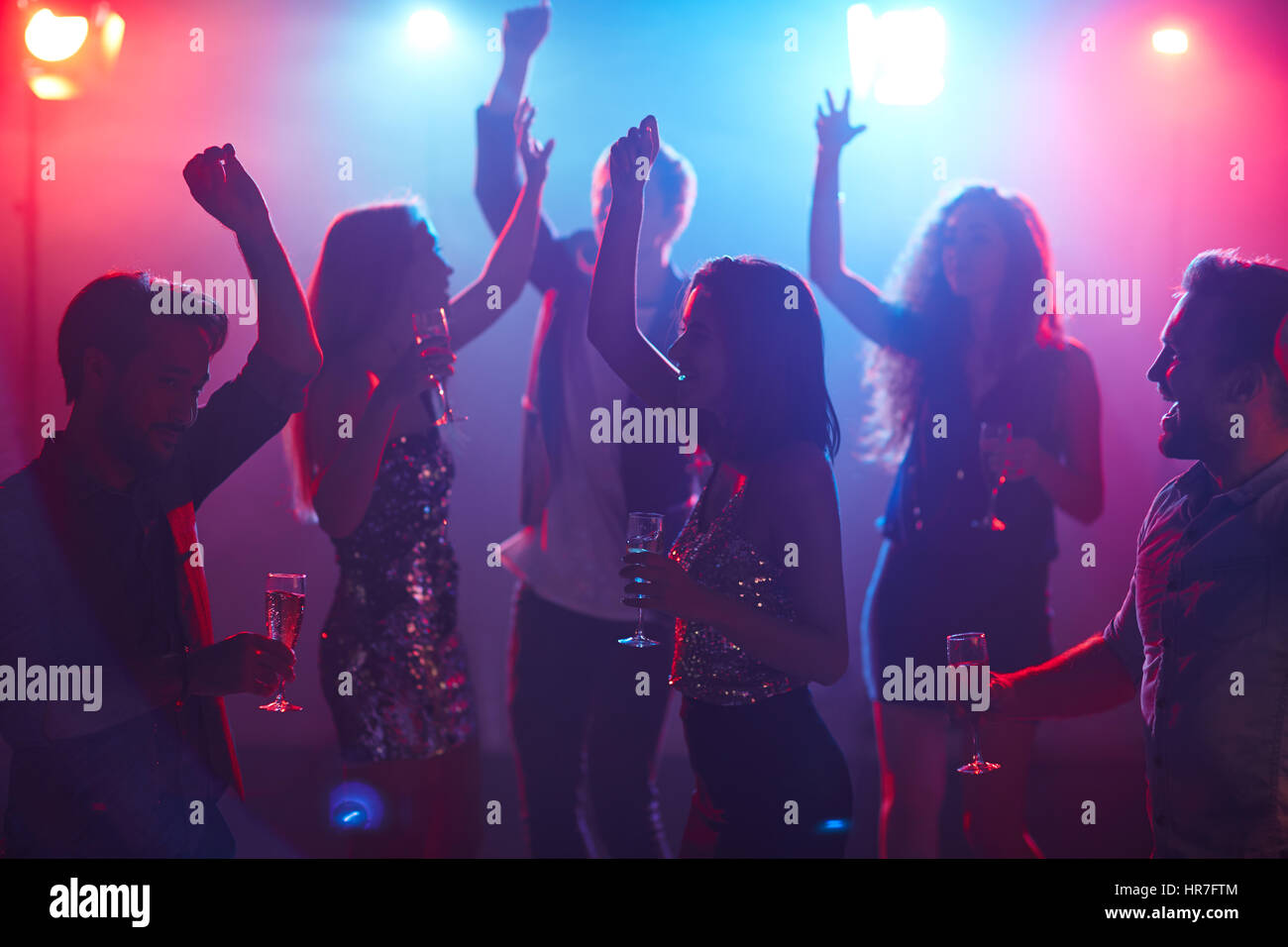 Happy students celebrating prom in night club, dancing with raised hands and holding glasses of champagne - Stock Image