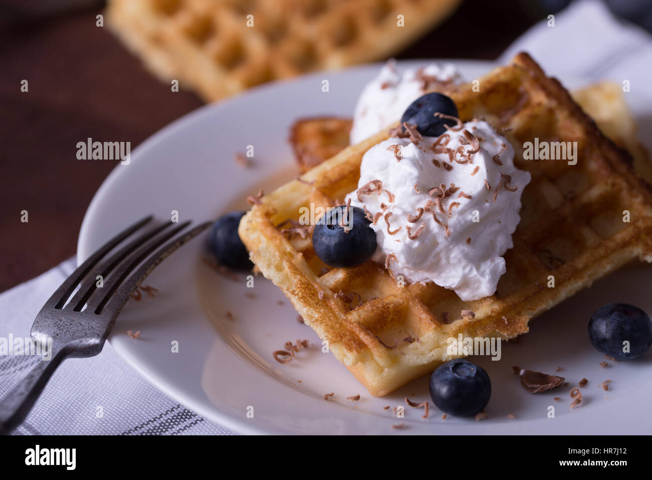 Belgian waffles on white plate, napkin and rustic background. - Stock Image