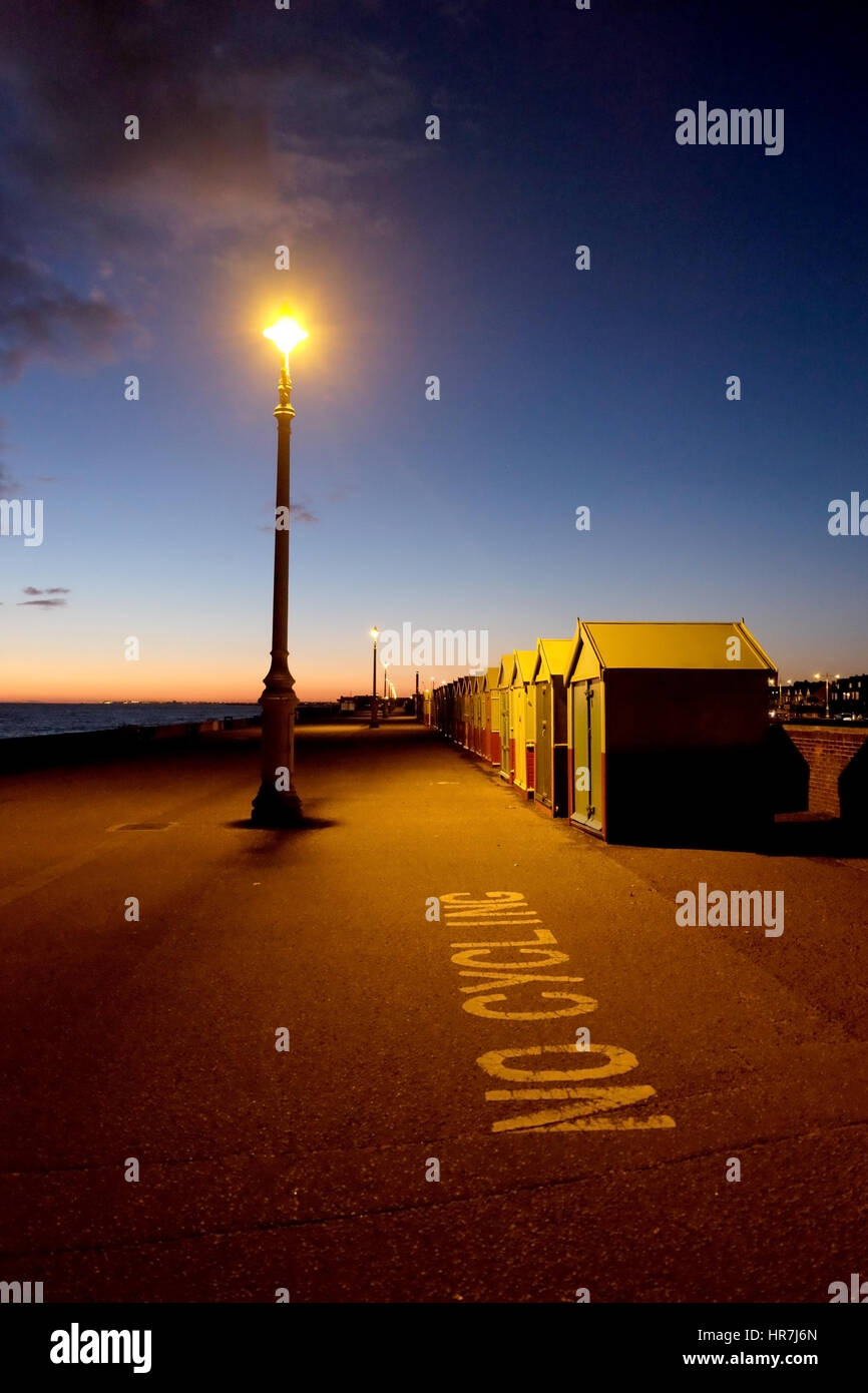 brighton seafront, white 'no cycling' sign written on the ground in the foreground, a row of colourful beach huts, - Stock Image