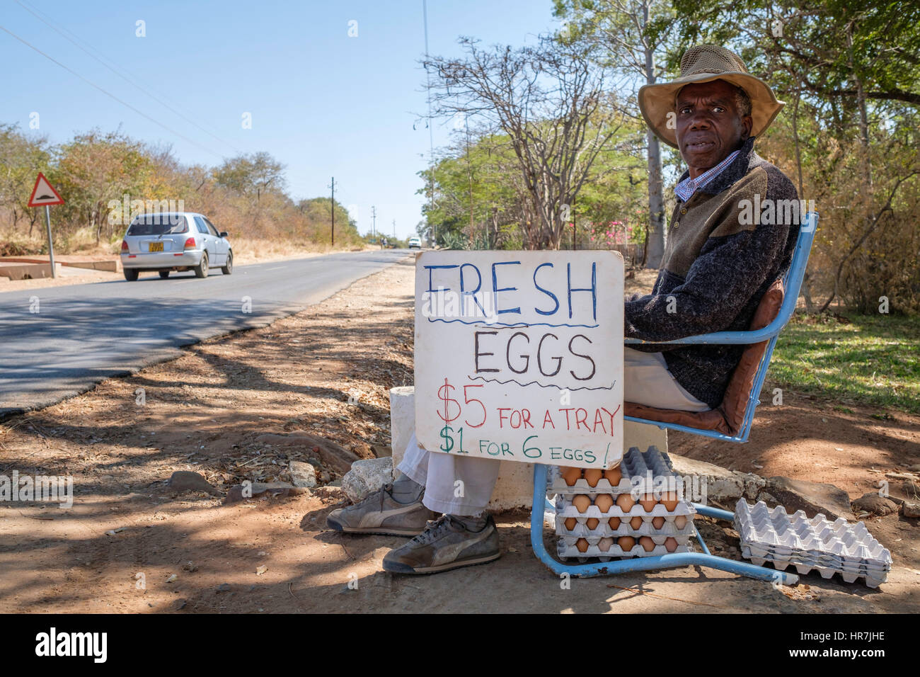 Old man selling eggs by the road. This man used to have his own touristic company but since the economic situation - Stock Image