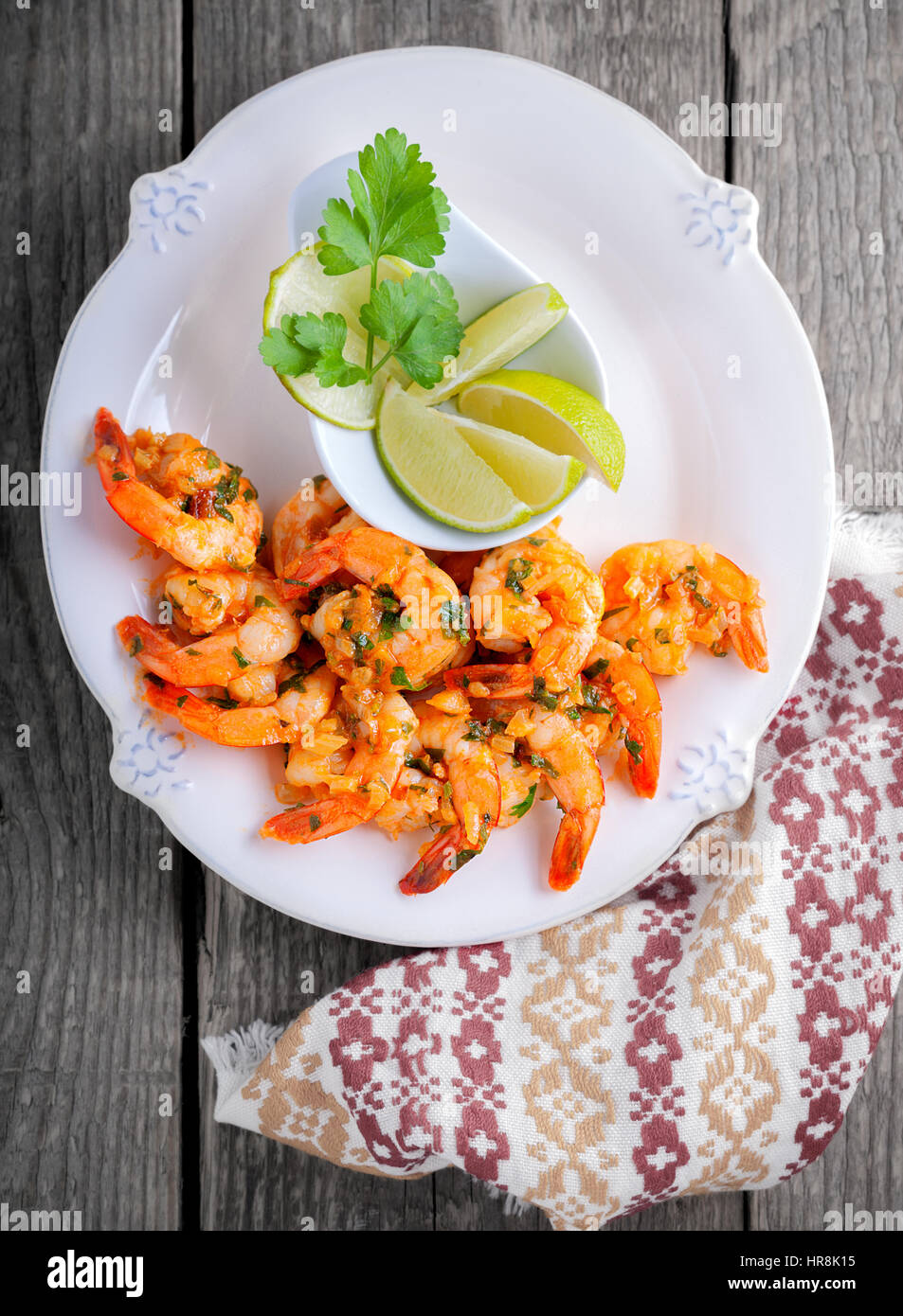 Fried Prawns with lemon served on a wooden surface. - Stock Image