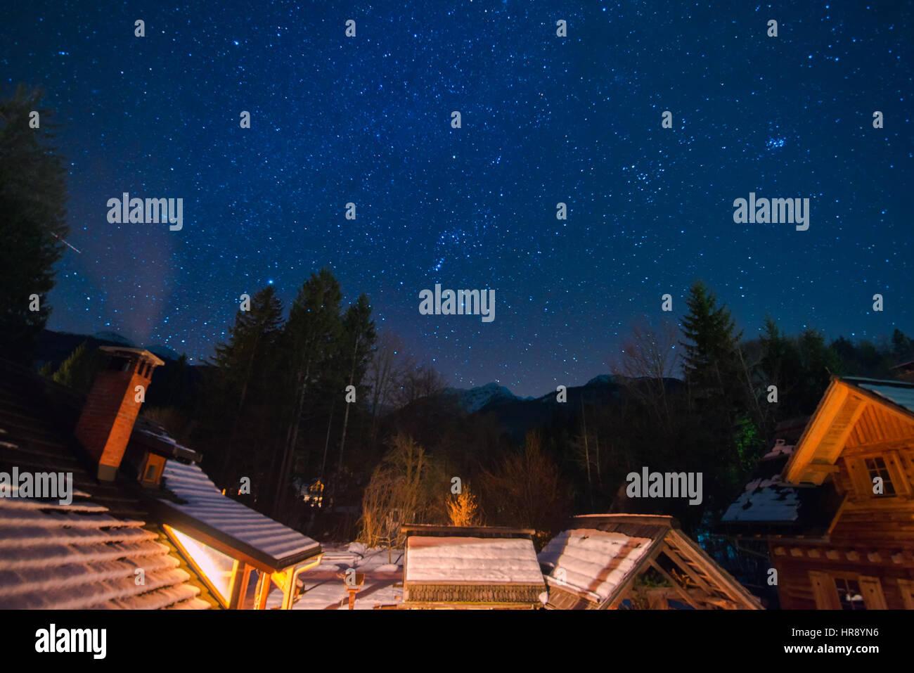 Night sky and stars above mountain cabins in winter, idyllic midnight scene - Stock Image