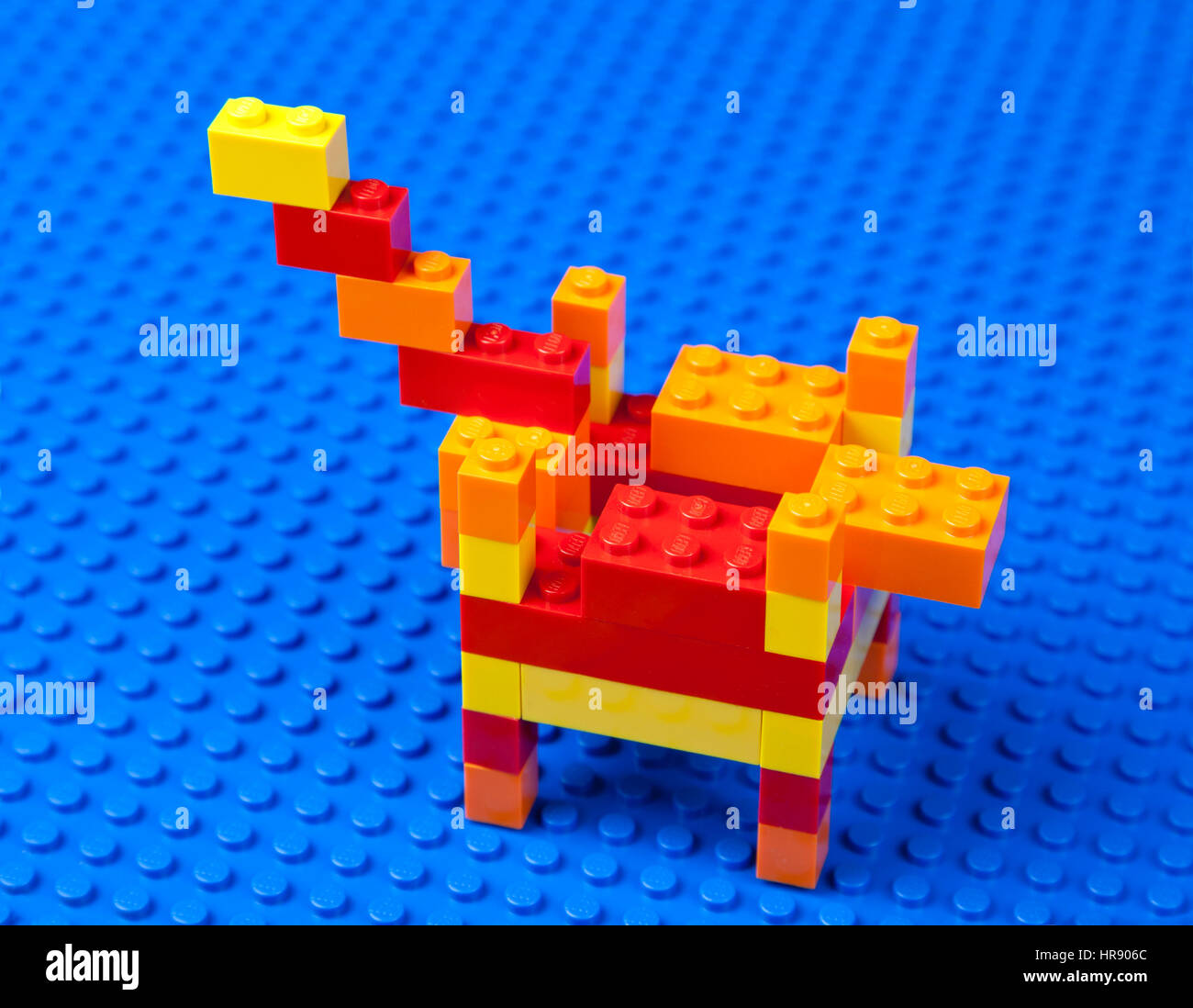 Colourful Lego brick model of an offshore oil platform on a blue Lego base plate - Stock Image