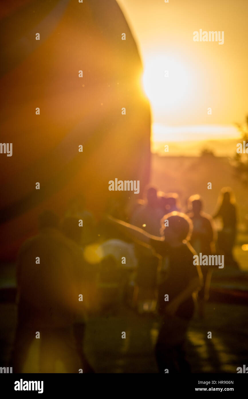 Sun rising behind the crowd on a chilly desert morning during the Colorado River Crossing Balloon Festival in the Stock Photo