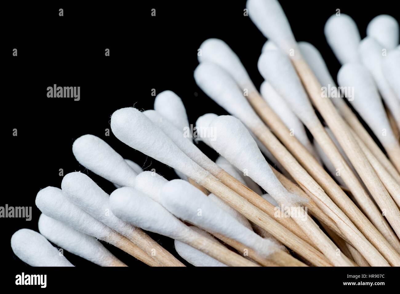 Pile of cotton swabs, q tips, spread out like a fan. The swabs are photographed against a black background Stock Photo