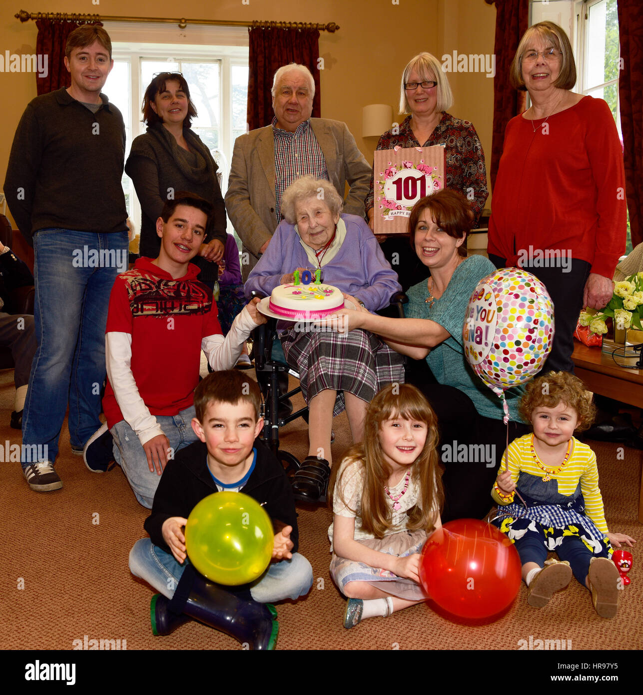 Elderly woman in wheelchair celebrating her 101st birthday surrounded by her extended family and staff members in - Stock Image