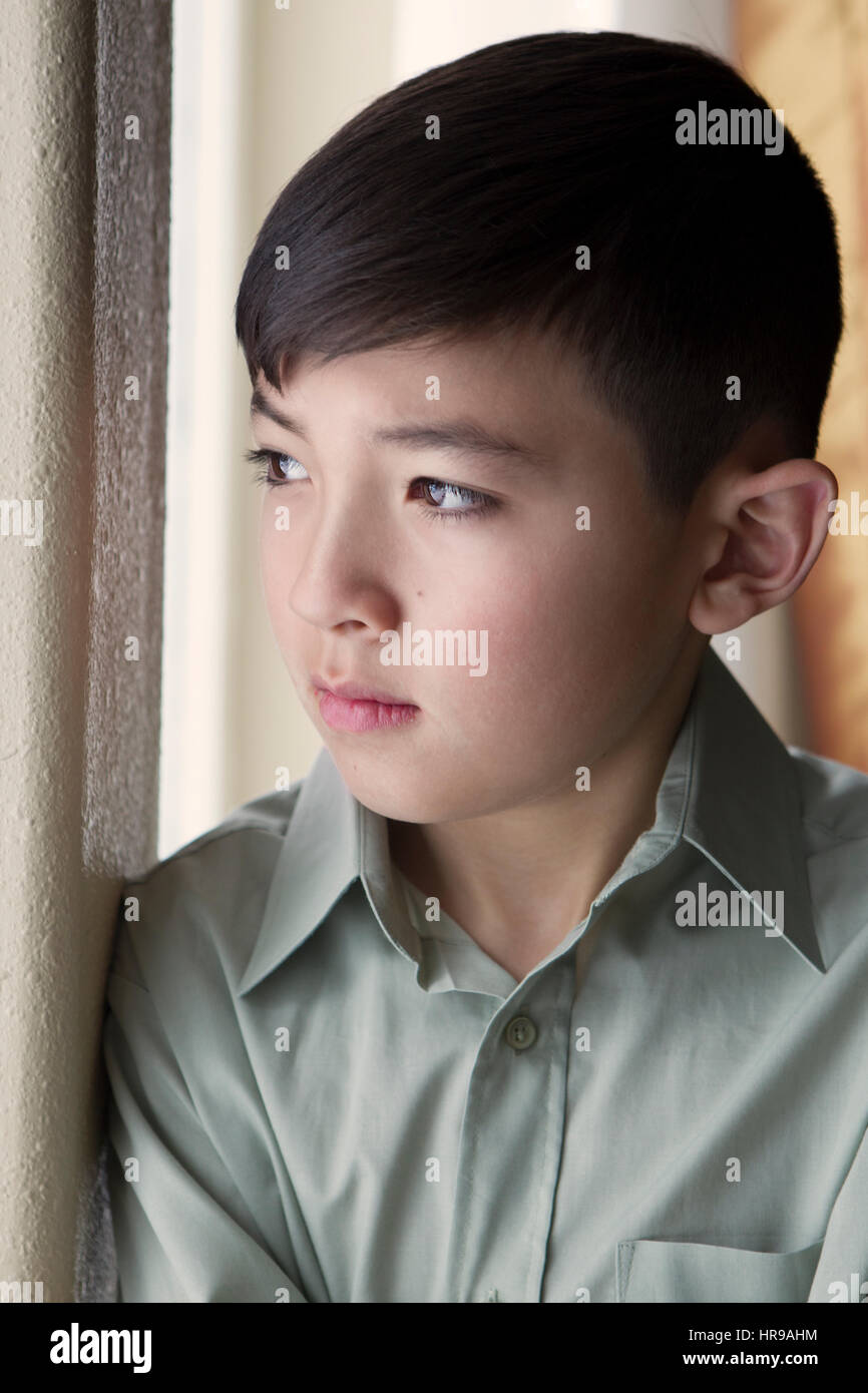 A young boy gazes out the window from inside. - Stock Image