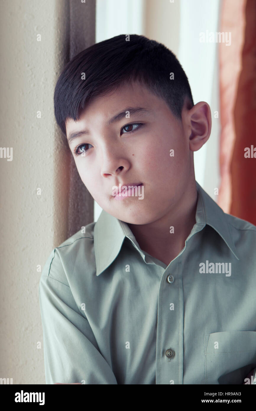 Young boy by a window in an emotional pose. - Stock Image
