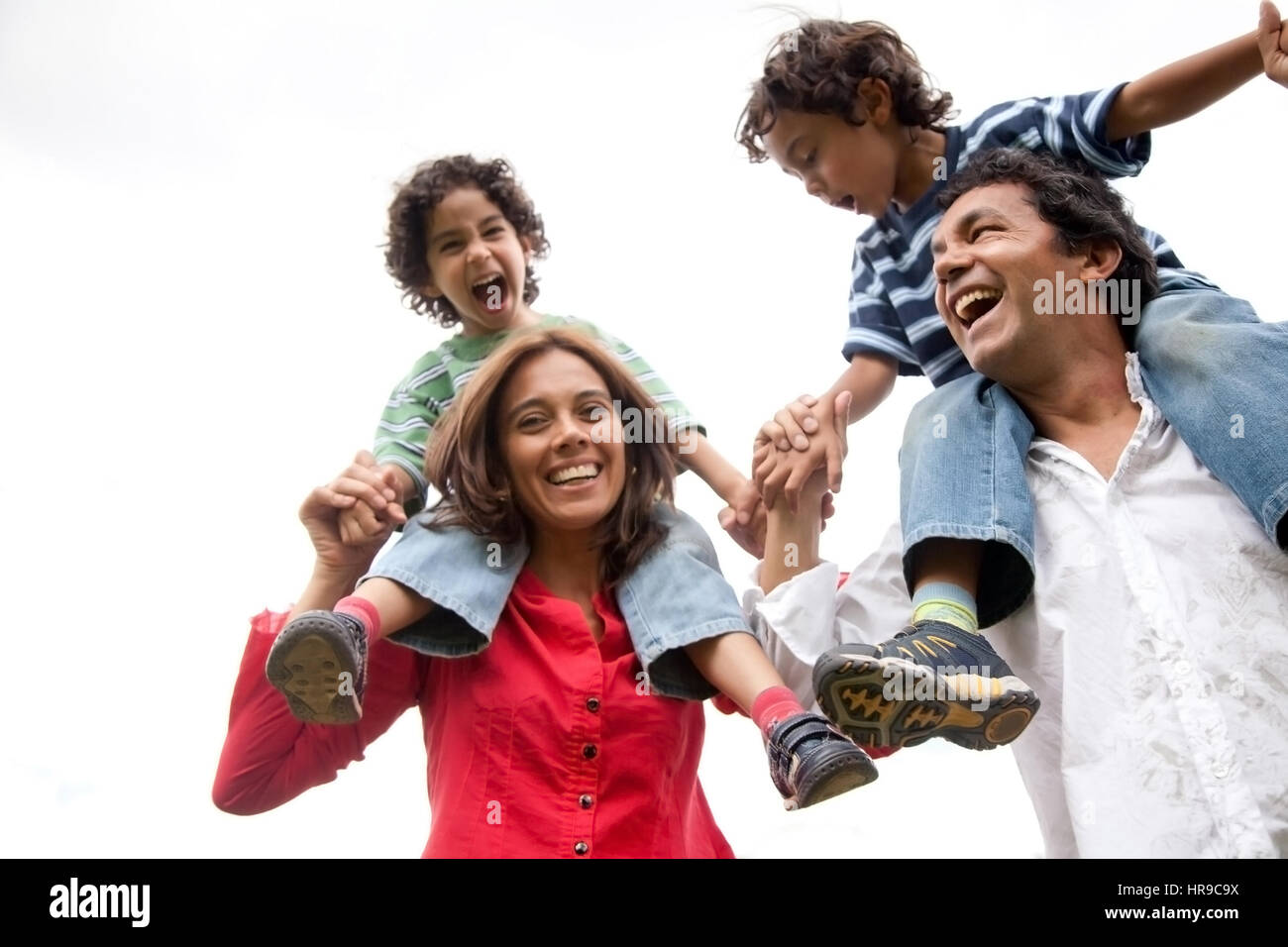 mother and father carrying their sons on their shoulders - Stock Image