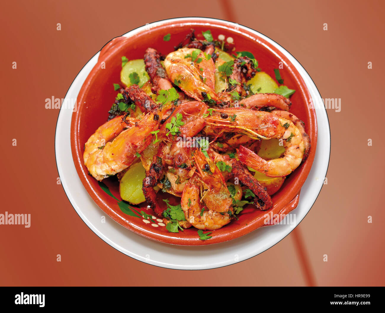 Close-up of a octopus and shrimp dish in a terracotta plate - Stock Image
