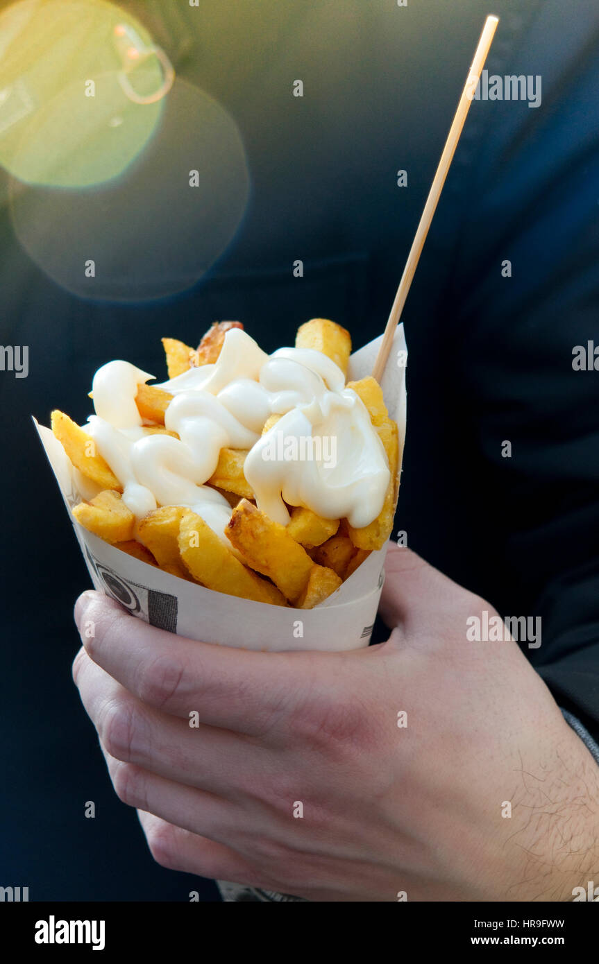 Hand Holding French Fries with Mayonnaise - Stock Image