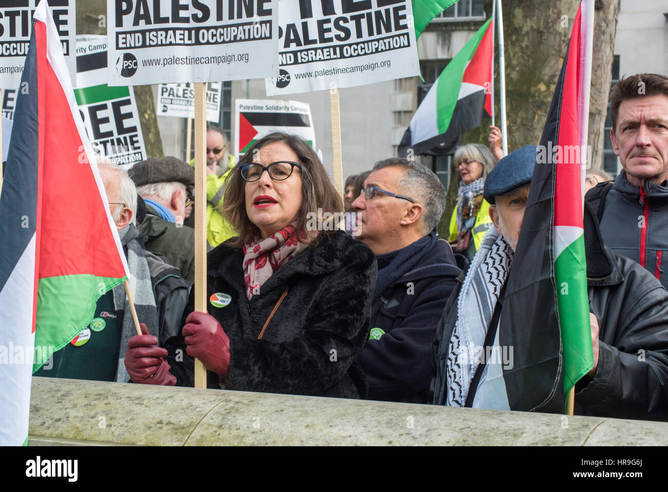 Demonstrators campaigning for Palestine in the street opposite Downing Street, London. - Stock Image