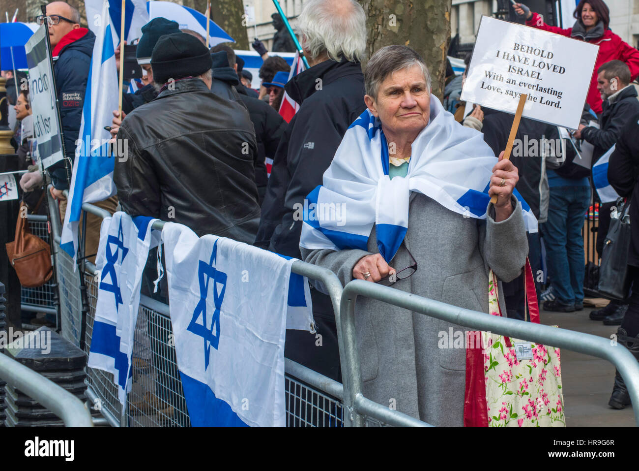 A senior woman  holding a poster supporting Israel standing behind a barrier with a flag bearing Israeli  flags. - Stock Image
