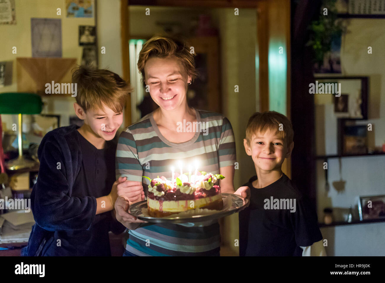 mother with two sons holding birthday cake - Stock Image