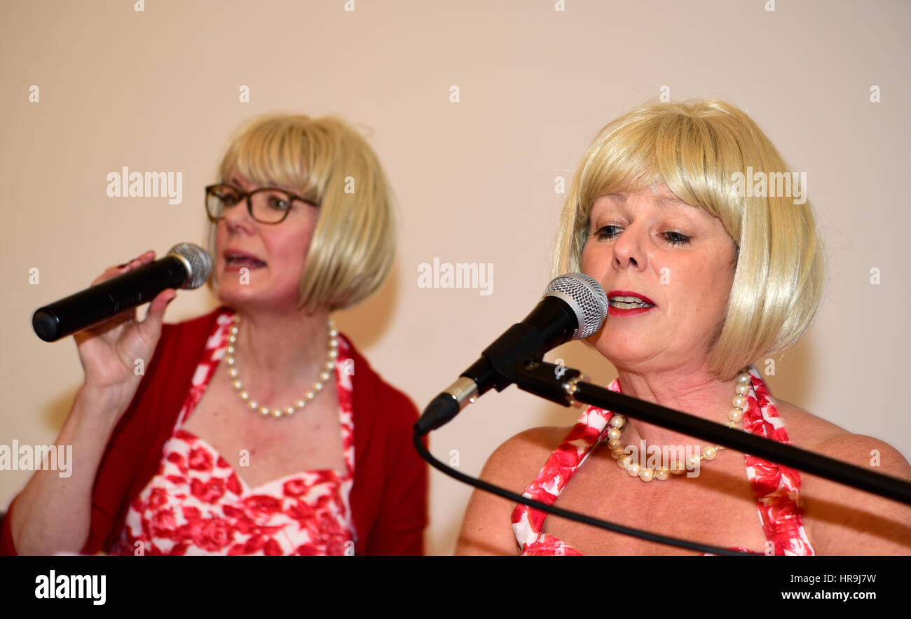 Female vocalists of local band - Out of the Shadows - performing popular songs from the 1960s at a community event - Stock Image