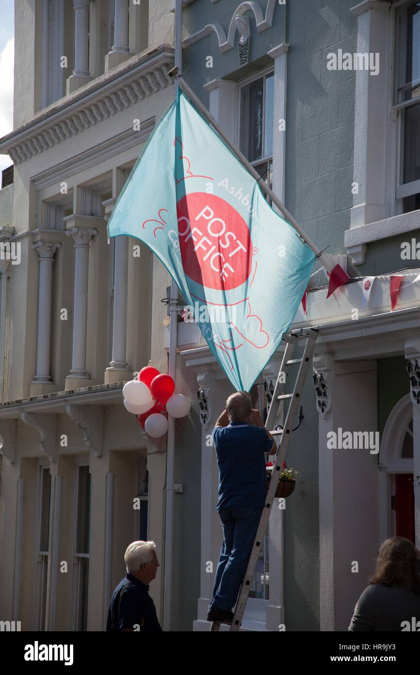 People hang a flag outside the newly refurbished Ashburton Post Office, Devon - Stock Image