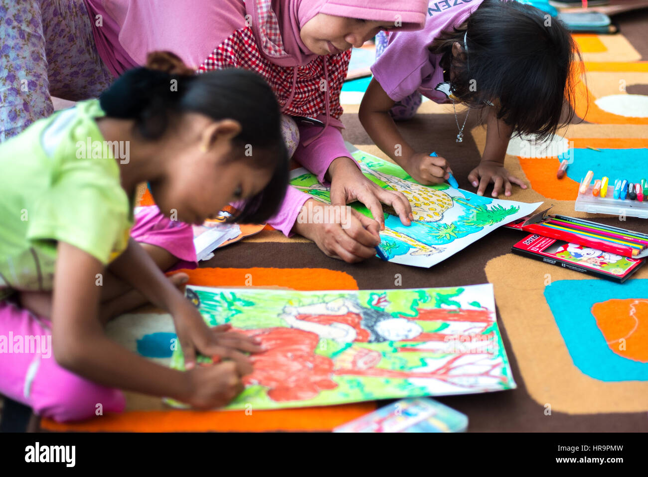 Female children drawing with mother. - Stock Image