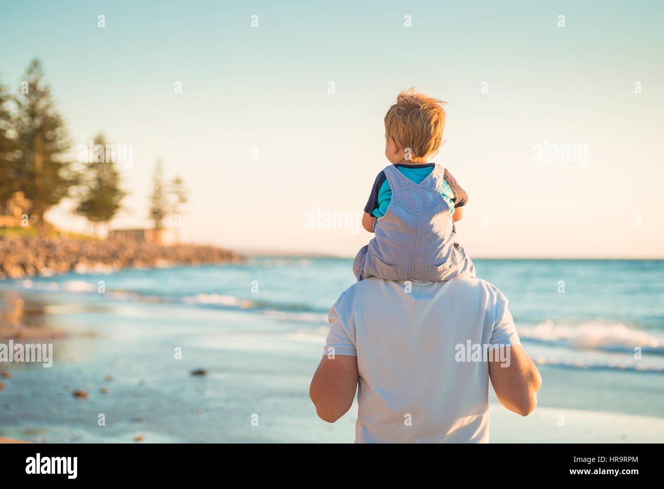 Father giving son piggyback ride on beach - Stock Image