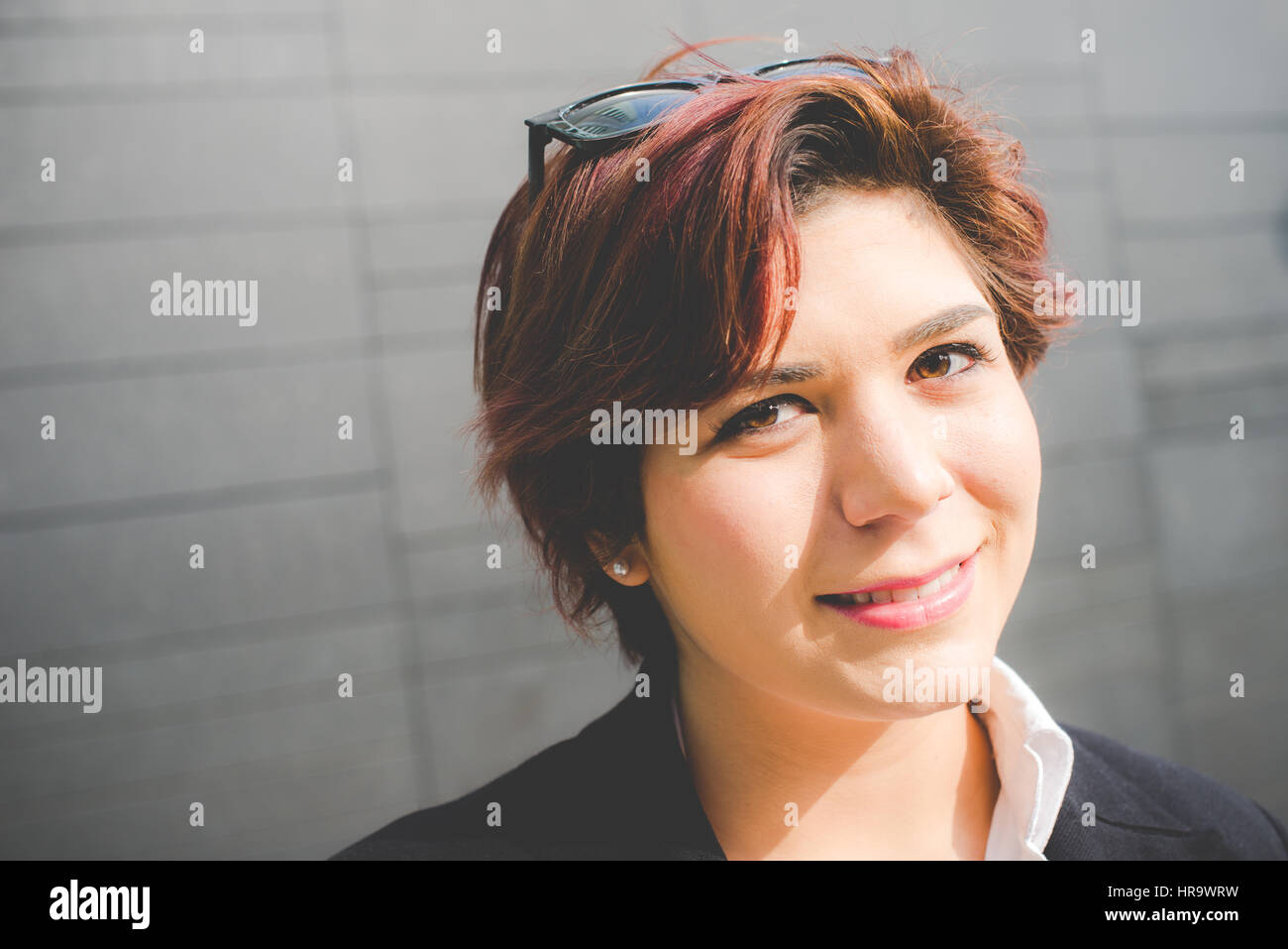 young authentic business woman smiling on modern wall background - Stock Image