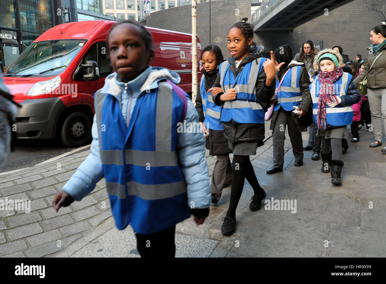 British school children group wearing blue vests walking along a street after a visit to the Museum of London England - Stock Image