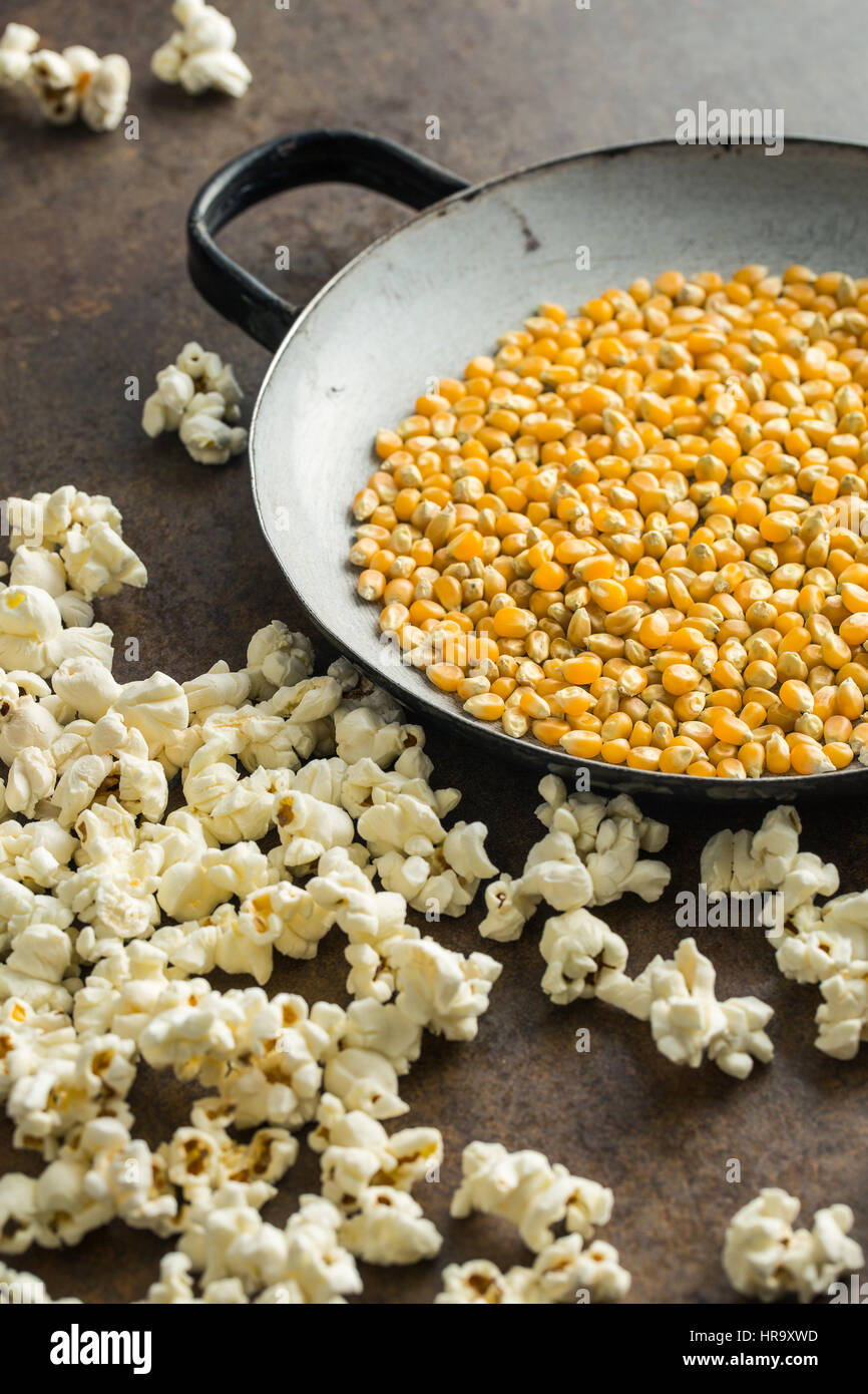 Popcorn and corn seeds on rusty background. - Stock Image