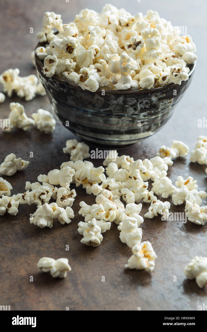 Popcorn in ceramic bowl on rusty background. - Stock Image