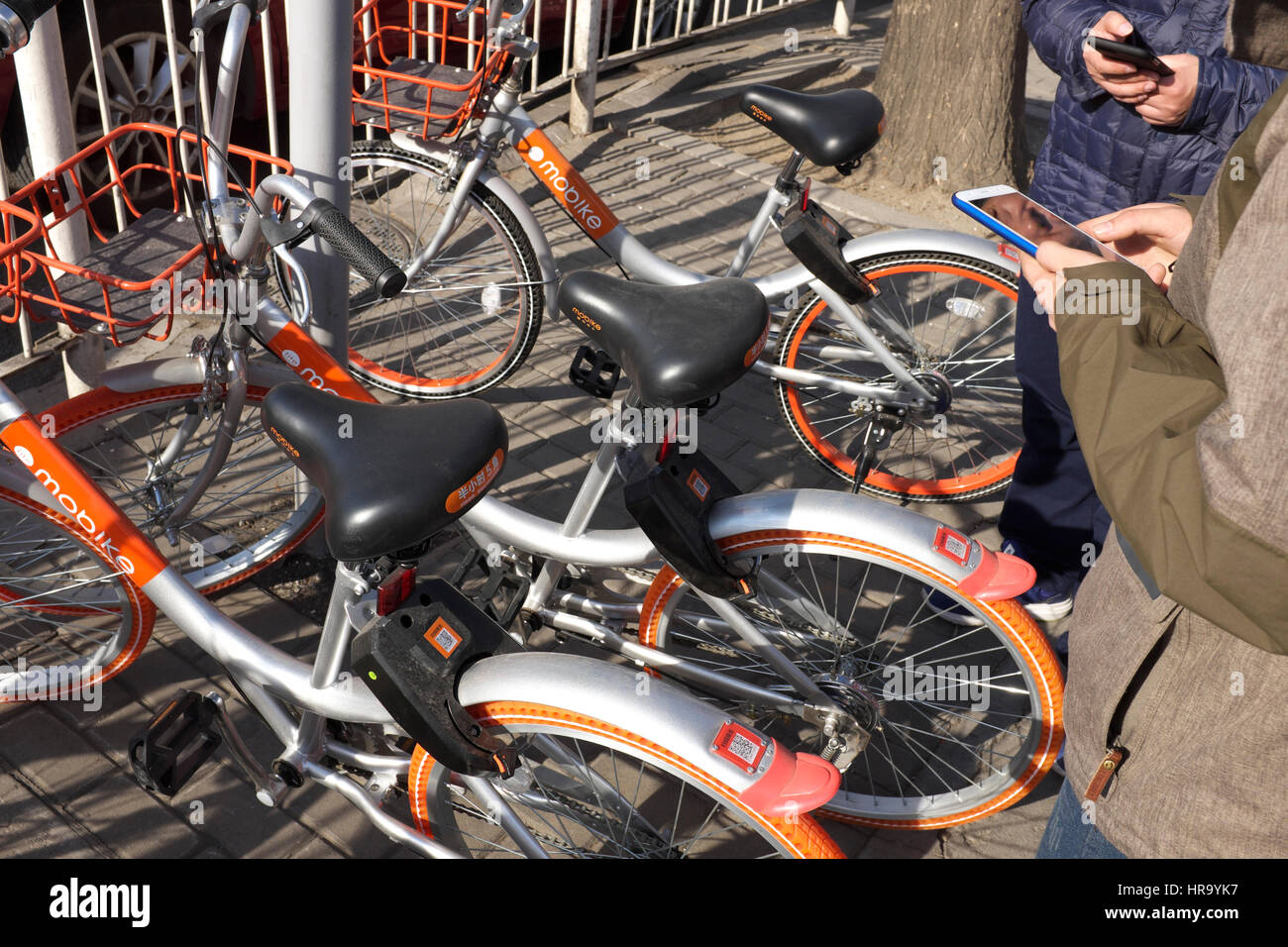 People use Bike-Sharing APP to rent bicycle in Beijing, China. 28-Feb-2017 - Stock Image