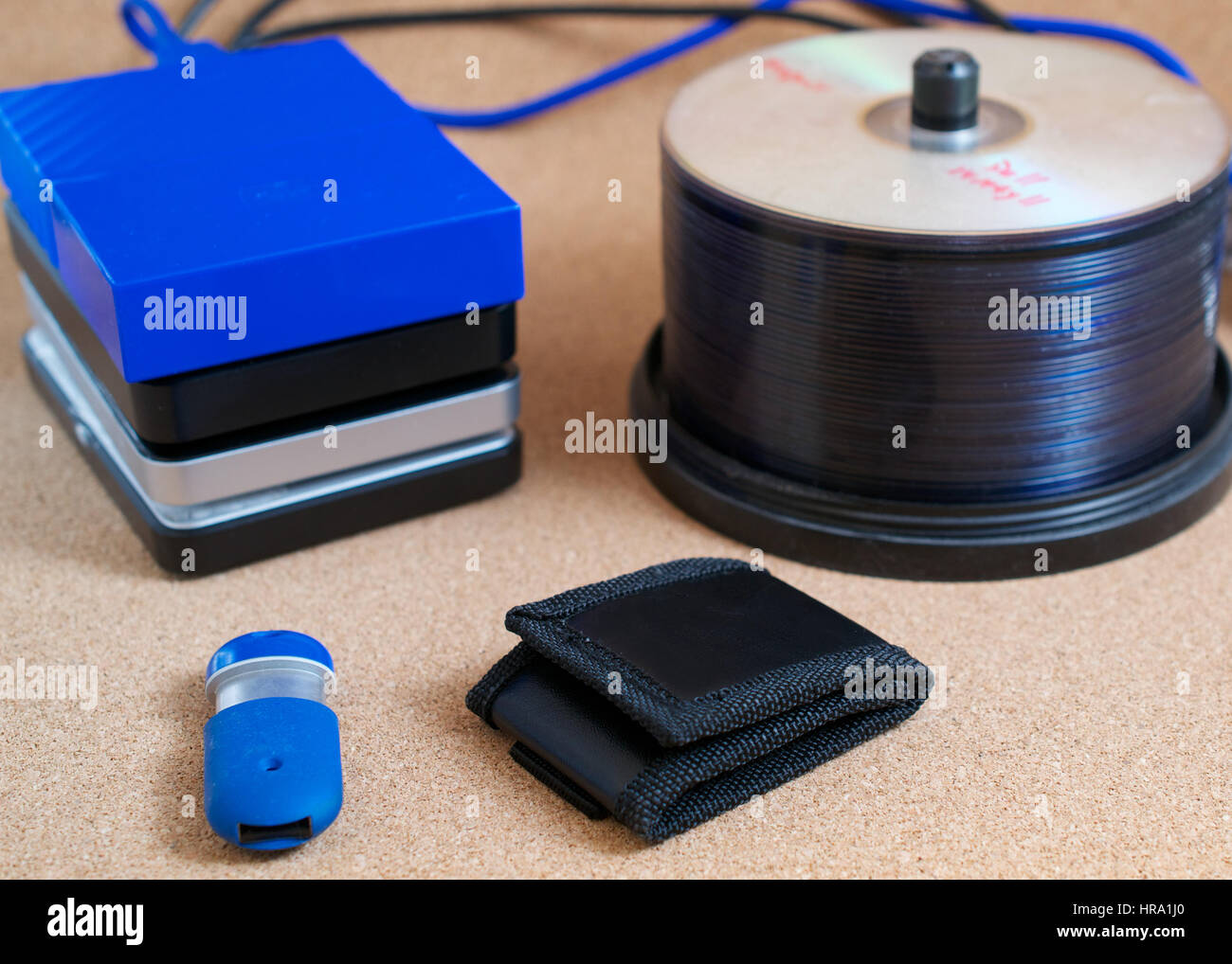Digital data backup devices: external USB hard drives, memory stick, memory card wallet and CDs on cork background - Stock Image