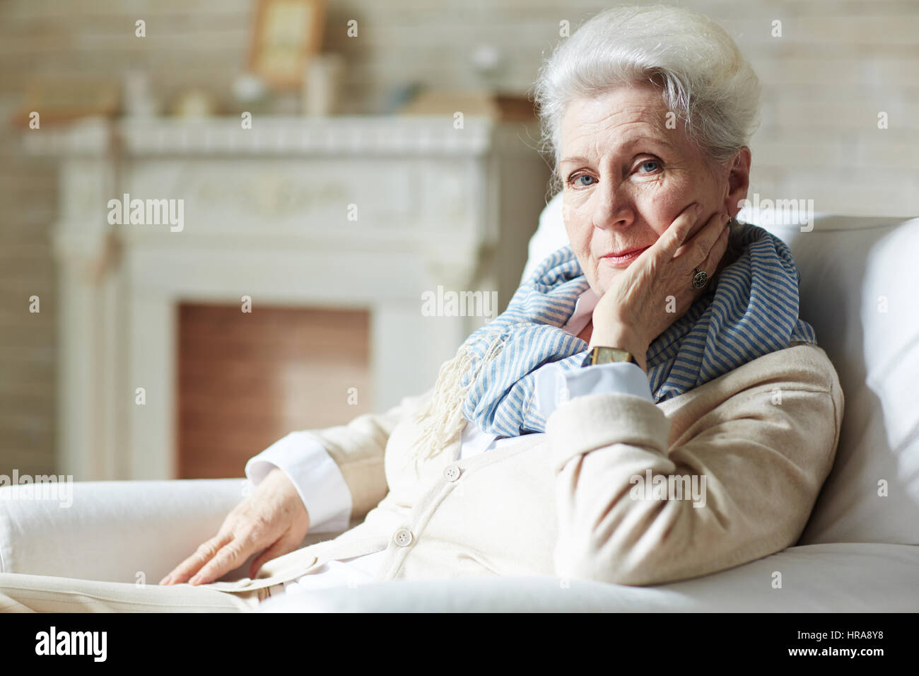 Pretty elderly woman in white shirt and beige cardigan leaning on elbow and looking at camera with slight smile - Stock Image