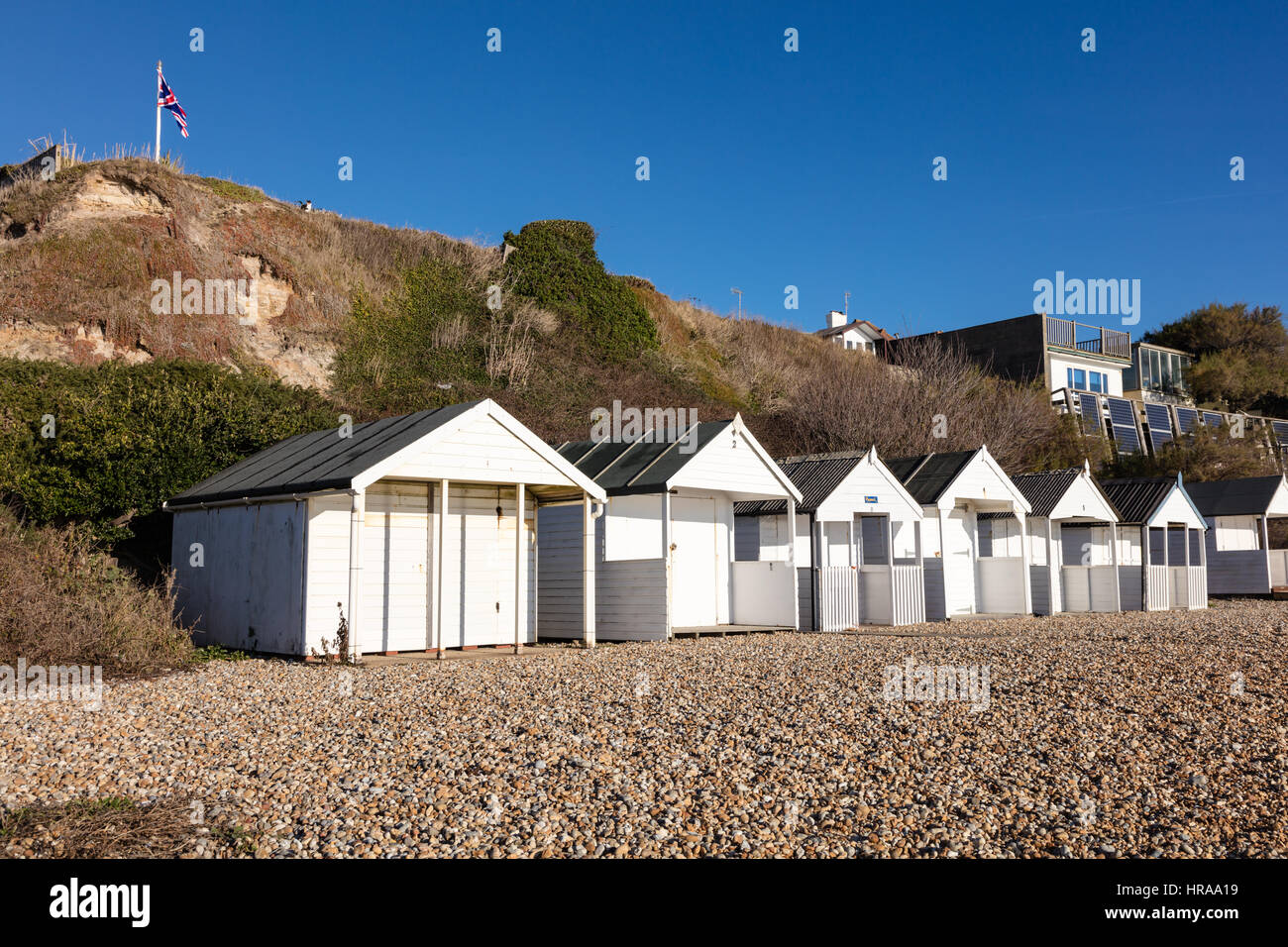 A row of beach huts under the cliffs at Bexhill on Sea, on the cliffs is a flagpole with a Union Flag under which - Stock Image
