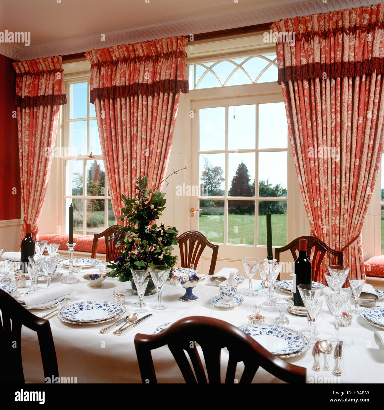 China and glassware in dining room with red patterned curtains and spectacular views to garden - Stock Image