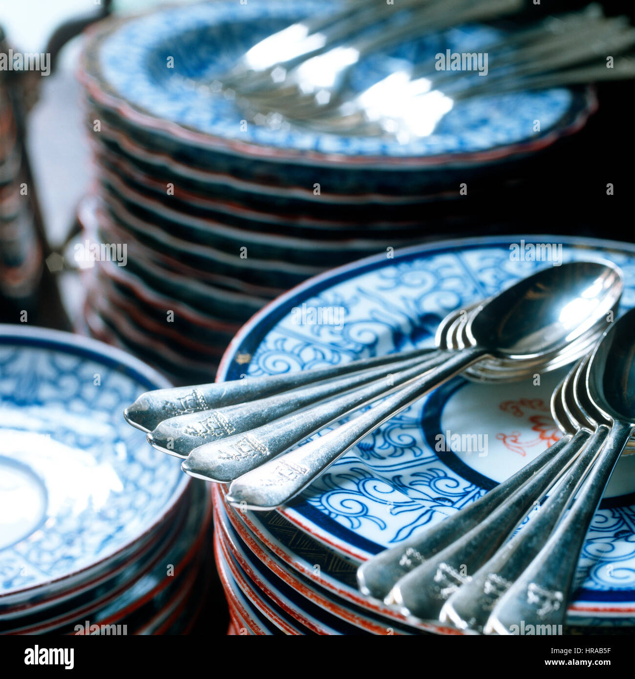 Silver teaspoons engraved with family crest on blue and white plates - Stock Image