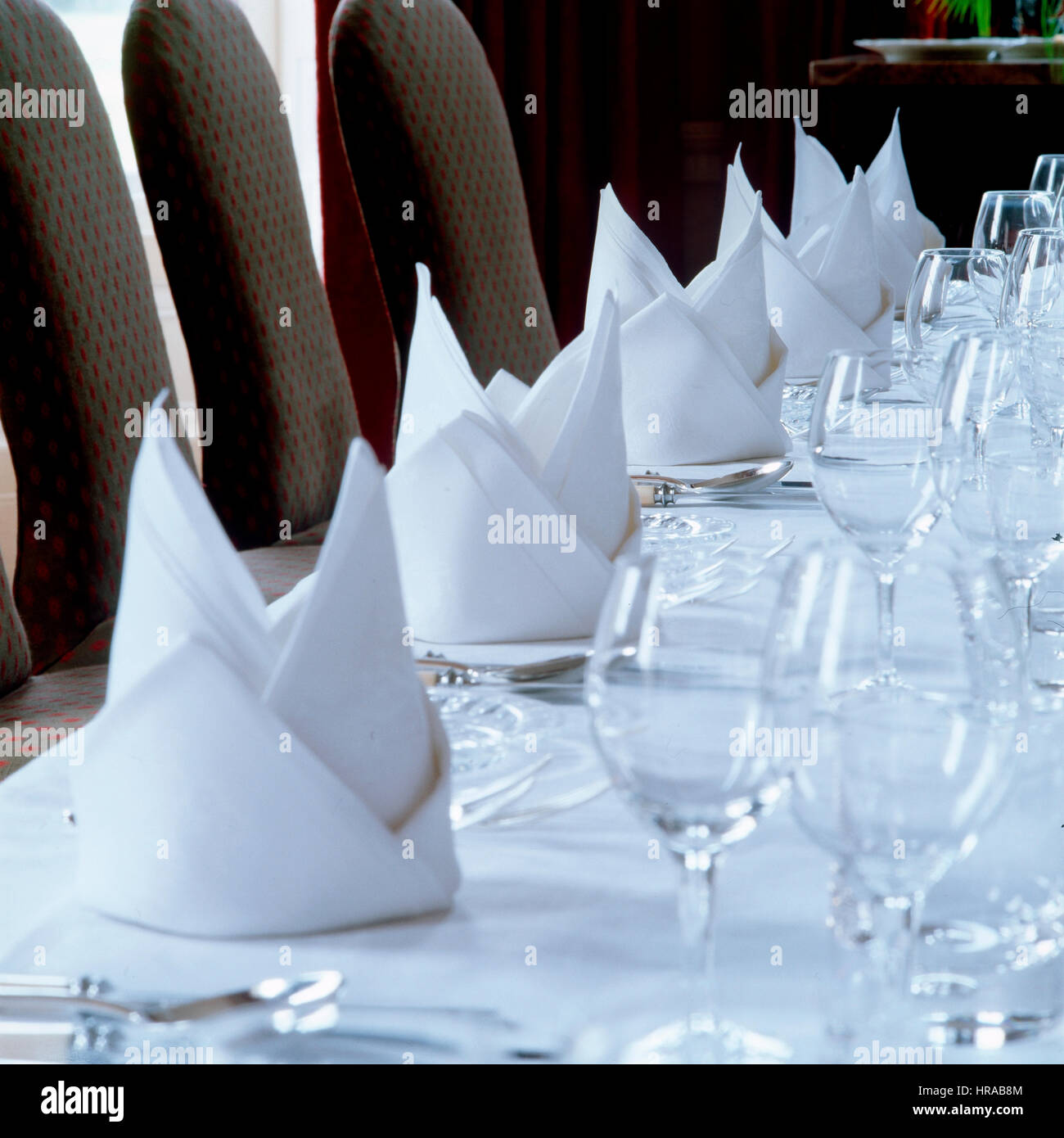 A set table with folded napkins. - Stock Image