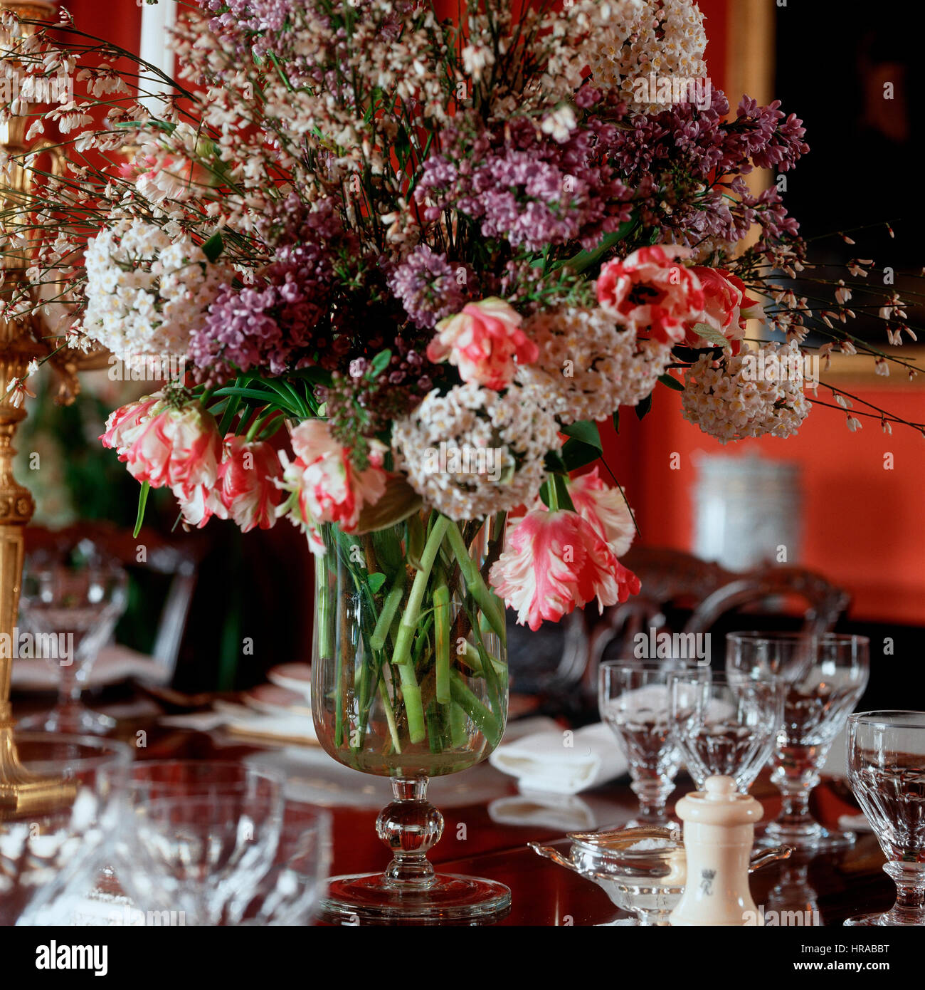 A vase of flowers on a dining table. - Stock Image