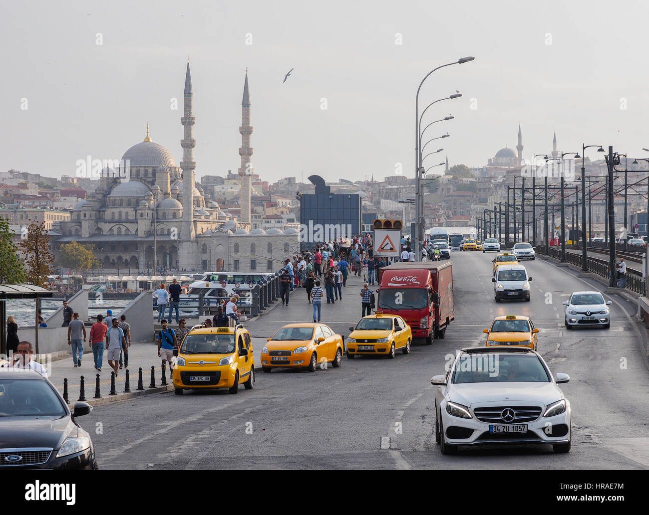 VIEW ACROSS THE GALATA BRIDGE WITH TAXIS IN FOREGROUND AND NEW MOSQUE IN BACKGROUND,GOLDEN HORN,  ISTANBUL TURKEY - Stock Image