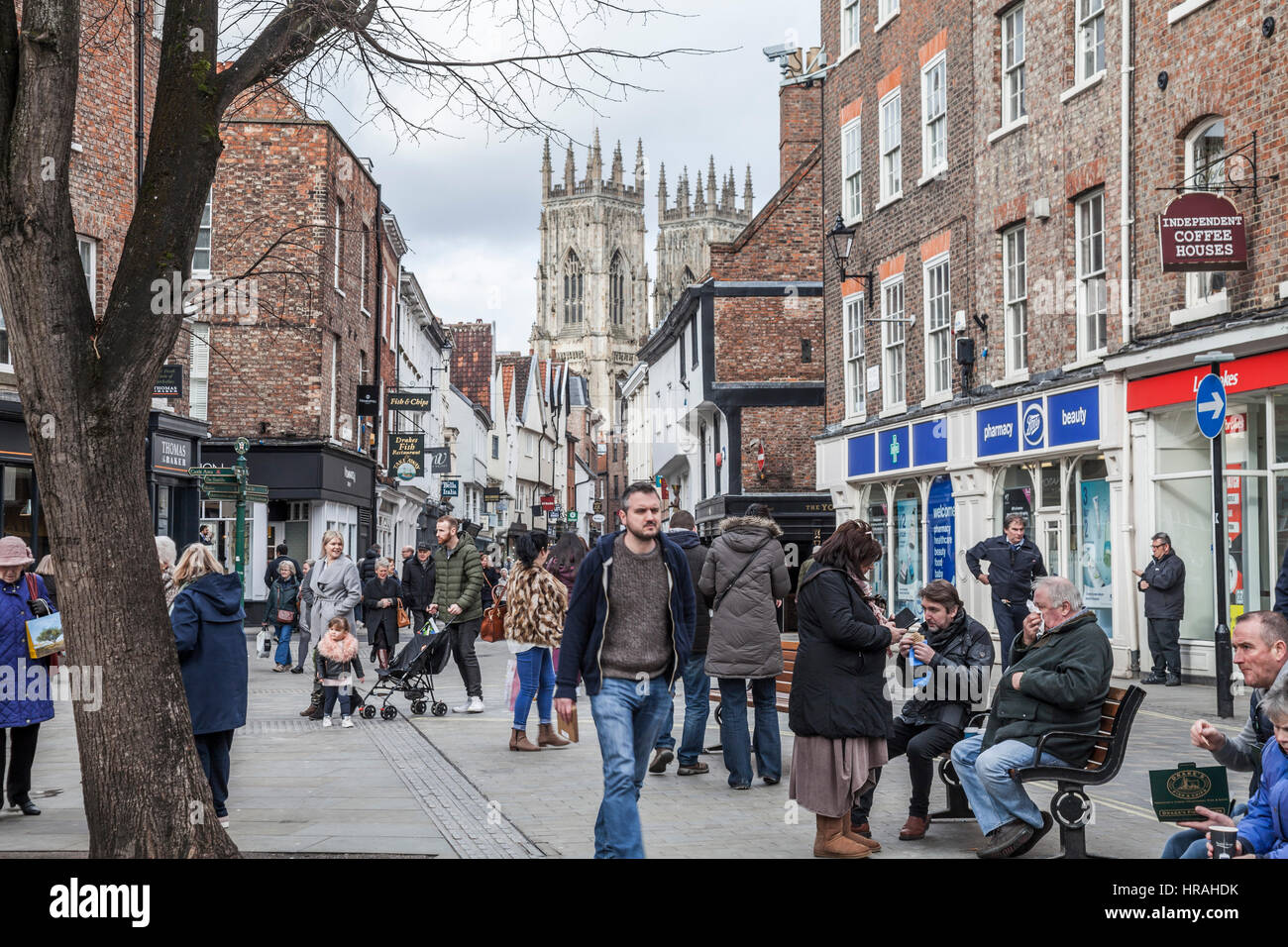 A view of the busy Low Petergate in York city center with the Minster in background - Stock Image