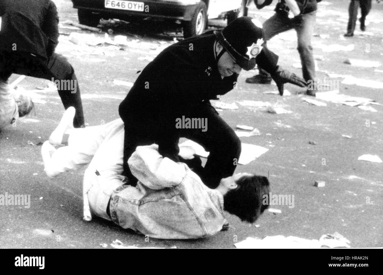 A police officer grapples with a protestor during the Poll Tax Riots in Trafalgar Square in London, England on March - Stock Image