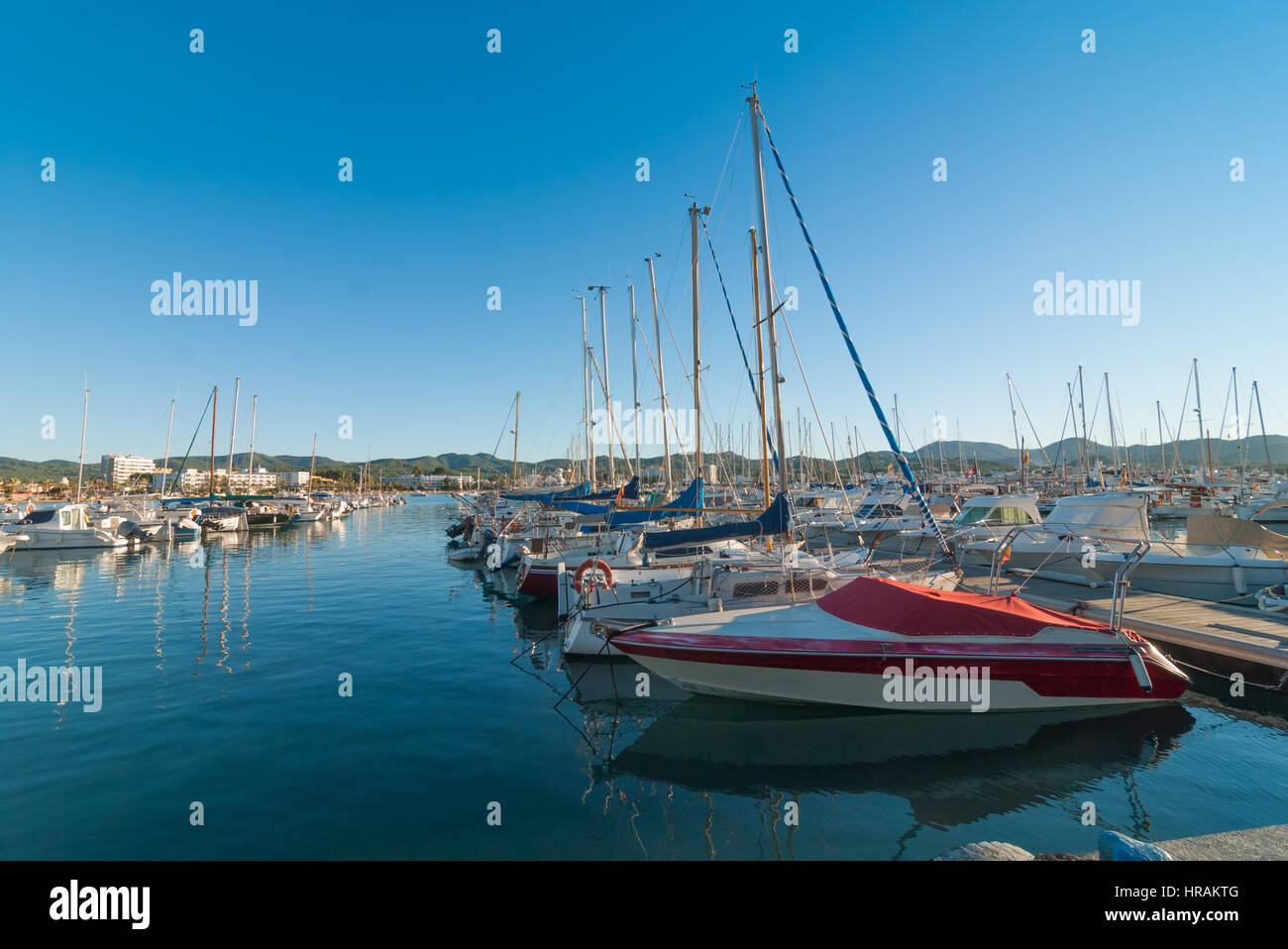 Ibiza sunshine in Late afternoon in St Antoni de Portmany, Ibiza, Spain.  Row of idle watercraft, sailboats & - Stock Image